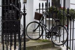 Bicyclette de cru avec le panier sur le porche Porte d'entrée au bâtiment résidentiel à Londres Porte typique dans le style angla image libre de droits