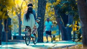Bicyclette de recyclage de personnes en parc pour l'exercice Photographie stock libre de droits