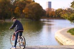 Bicyclette de tour de garçon d'adolescent sur le landscapce de chute de fond de lac de parc de ville image libre de droits