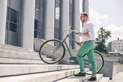 Bicyclette de transport de jeune homme d'affaires élégant vers le haut des étapes Photo stock