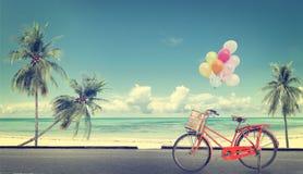 Bicyclette de vintage avec le ballon sur le ciel bleu de plage Photographie stock libre de droits
