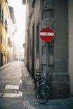 Bicyclette enchaînée à un pôle de signe images stock