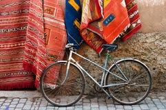 Bicyclette et tapis sur la rue du Maroc Image libre de droits