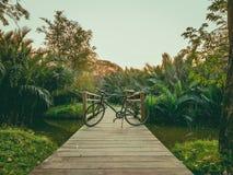 18 - Bicyclette faisant un cycle le soir sur un petit pont à travers le canal photographie stock