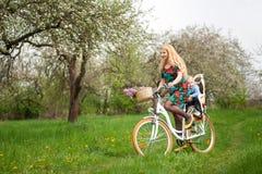 Bicyclette femelle blonde de ville d'équitation avec le bébé dans la chaise de bicyclette Images stock