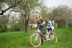 Bicyclette femelle blonde de ville d'équitation avec le bébé dans la chaise de bicyclette Image stock