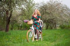 Bicyclette femelle blonde de ville d'équitation avec le bébé dans la chaise de bicyclette Photographie stock libre de droits