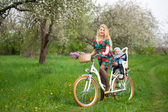 Bicyclette femelle blonde de ville d'équitation avec le bébé dans la chaise de bicyclette Photos stock