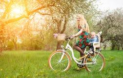 Bicyclette femelle blonde de ville d'équitation avec le bébé dans la chaise de bicyclette Images libres de droits