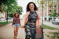 Bicyclette heureuse d'équitation de jeune femme sur la rue de ville Photographie stock