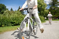 Bicyclette heureuse d'?quitation d'homme sup?rieur au parc d'?t? photographie stock