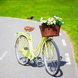 Bicyclette jaune de vintage avec des fleurs dans le panier en osier Photos stock