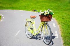 Bicyclette jaune de vintage avec le bouquet des fleurs dans le panier en osier Photo libre de droits