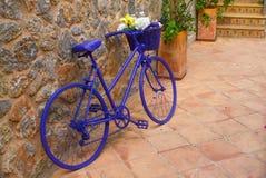 Bicyclette pourpre se penchant contre le mur Image libre de droits