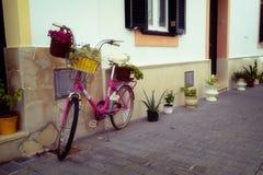 Bicyclette rose avec des fleurs près du mur de la maison Image libre de droits