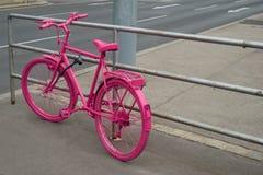 Bicyclette rose verrouillée à la balustrade Photo libre de droits