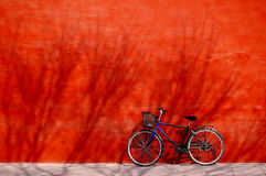 Bicyclette sous le mur rouge Photographie stock libre de droits