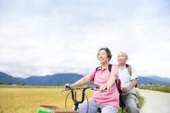 Bicyclette supérieure d'équitation de couples sur la route de campagne photos stock