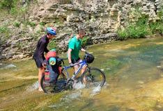 Bicyclette trafiquée deux par cyclistes au-dessus d'une rivière de montagne images libres de droits