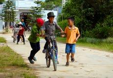 Bicyclette vietnamienne de tour d'enfants sur la route de campagne Image stock