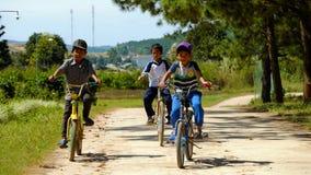 Bicyclette vietnamienne de tour d'enfants sur la route de campagne Images stock