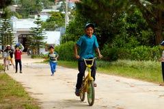 Bicyclette vietnamienne de tour d'enfants sur la route de campagne Photo stock