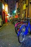 Bicyclettes colorées dans une rangée à l'extérieur du beau secteur de lumières rouges célèbre de Kabukicho, entourage de grand Photo stock