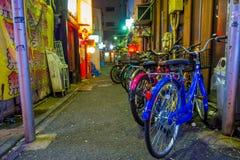 Bicyclettes colorées dans une rangée à l'extérieur du beau secteur de lumières rouges célèbre de Kabukicho, entourage de grand Photos libres de droits