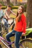 Bicyclettes d'équitation d'adolescente avec ses amis Images libres de droits
