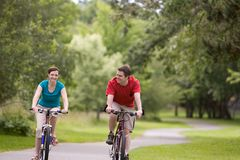 Bicyclettes d'équitation de couples au stationnement - horizontal Images stock