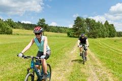 Bicyclettes de montagne d'équitation de couples de sport dedans Photographie stock