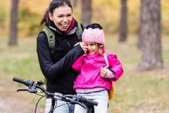 Bicyclettes de monte heureuses de mère et de fille images stock