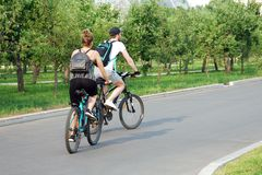 Bicyclettes de monte de jeunes couples en parc d'été images stock