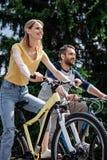 Bicyclettes de sourire d'équitation de couples ensemble au parc Image libre de droits
