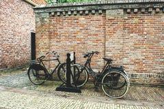 Bicyclettes près d'un mur de briques Images stock