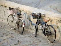 Bicyclettes stationnées de dames par le mur en pierre Photo stock