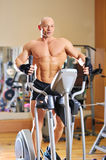 Bicyclettes stationnaires. Homme de forme physique Photos stock