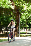 Bicycling. Girl cycling in the park. She's wearing white sport clothes, cap, her bicycle is red. It's a sunny summer day Royalty Free Stock Photo
