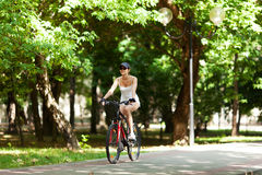 Bicycling. Girl cycling in the park. She's wearing white sport clothes, cap, her bicycle is red. It's a sunny summer day Stock Photo