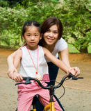 Bicycling. Asian girl learns to ride bicycle stock photo
