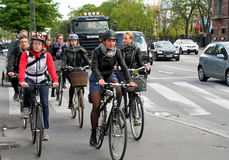 Bicycling in Copenhagen. People bicycling in Copenhagen among cars and trucks Stock Image
