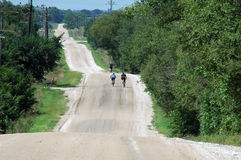Bicycling on country road. Men riding bicycles on rural dirt road in the countryside Royalty Free Stock Images