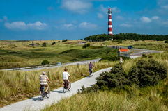 Bicycling in dunes. People on vacation riding bicycle in the dunes of Ameland, Netherlands Royalty Free Stock Photos