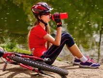 Bicycling dziewczyna jest ubranym hełma pić butelki woda Zdjęcia Stock