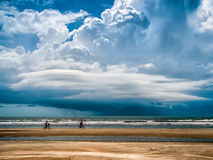 Bicycling fun on the beach. Two vacationers enjoy bicycling on a beach shortly before a large storm arrives from the sea Stock Photos