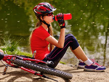 Bicycling girl wearing helmet drinking of bottle water. Stock Photos