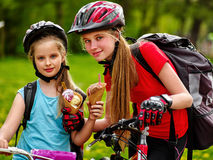 Bicycling girls with rucksack eating ice cream cone in park. Girls sisters wearing bicycle helmet and gloves with rucksack rides bicycle. Girls children are Royalty Free Stock Photos