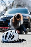 Bicycling helmet on the asphalt after accidental collision. Between the bicycle of a sorrowful young woman and a 4x4 car in the city stock photography
