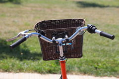 Bicycling in the park. Orange road bike with a basket at the helm.Bicycle in a park in the parking lot stock photo