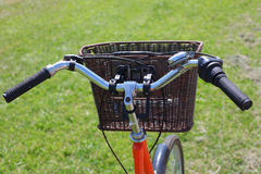 Bicycling in the park. Orange road bike with a basket at the helm.Bicycle in a park in the parking lot stock images